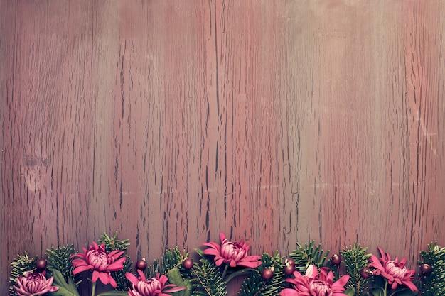 Il crisantemo di borgogna fiorisce sulla tavola presentata con le decorazioni dell'inverno, spazio della copia