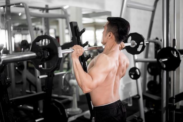Il culturista muscolare dell'uomo di forma fisica è allenamento in palestra