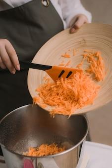 Il cuoco aggiunge le carote grattugiate alla ciotola di metallo. la mano femminile ha messo la carota tagliata in ciotola di legno con insalata in cucina. cucinare le verdure