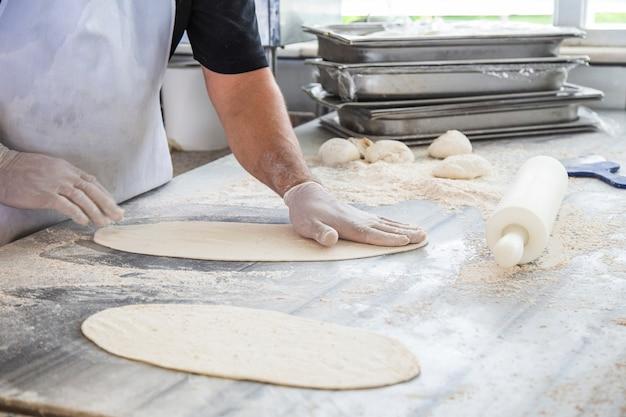 Il cuoco che prepara la carne tritata di focaccia. processo di produzione di focaccia