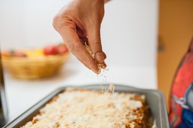 Il cuoco cosparge il formaggio grattugiato sul piatto. restiamo a casa e cuciniamo le lasagne.