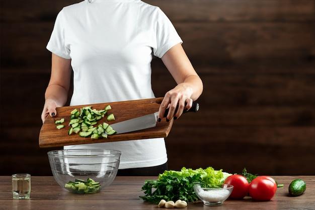 Il cuoco della donna taglia le verdure per la preparazione dell'insalata su legno.