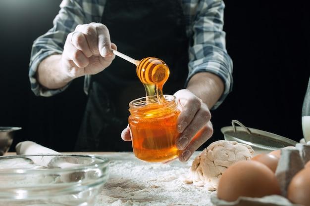 Il cuoco maschio professionista spruzza la pasta con farina, i preapares o cuoce il pane al tavolo da cucina