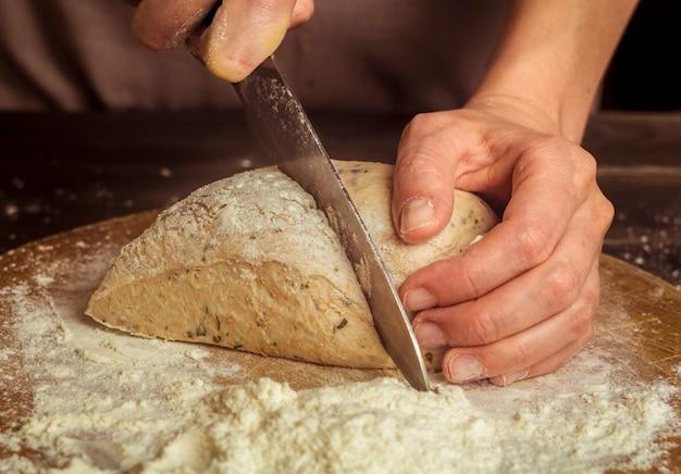 Il cuoco taglia la pasta cruda