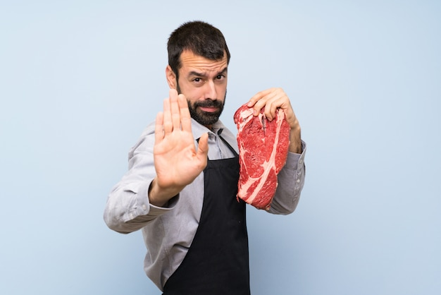 Il cuoco unico che tiene una carne cruda che fa il gesto di arresto e deludente