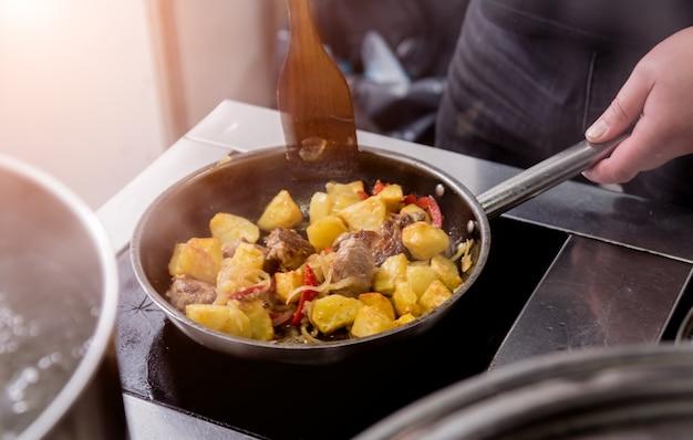 Il cuoco unico cucina le patate fritte con i pezzi di carne in una cucina del ristorante