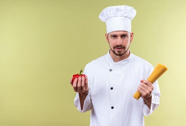 Il cuoco unico maschio professionista soddisfatto cucina in uniforme bianca e cappello del cuoco che tiene il peperone fresco e della pasta degli spaghetti crudi che sta sopra il fondo verde