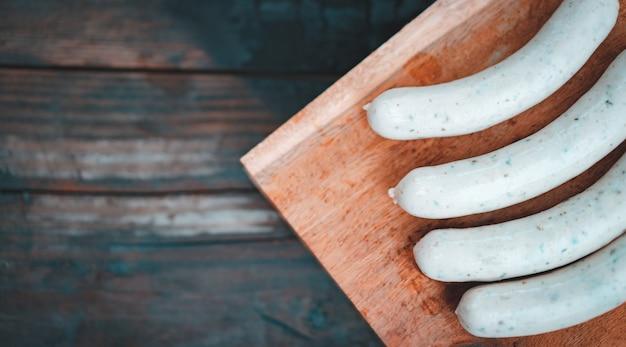 Il cuoco unico prepara la salsiccia di maiale sul bordo di legno