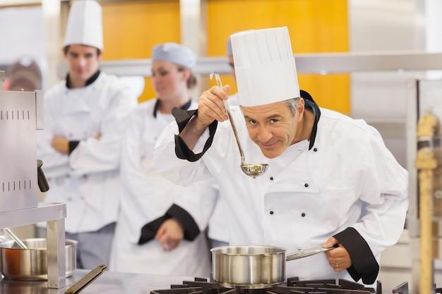 Il cuoco unico sorridente che assaggia i suoi studenti lavora