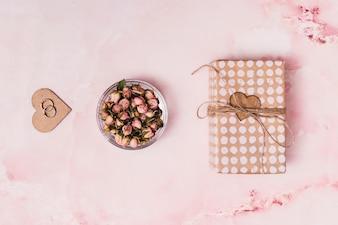 Il cuore dell'ornamento con gli anelli vicino fiorisce dentro può e scatola attuale