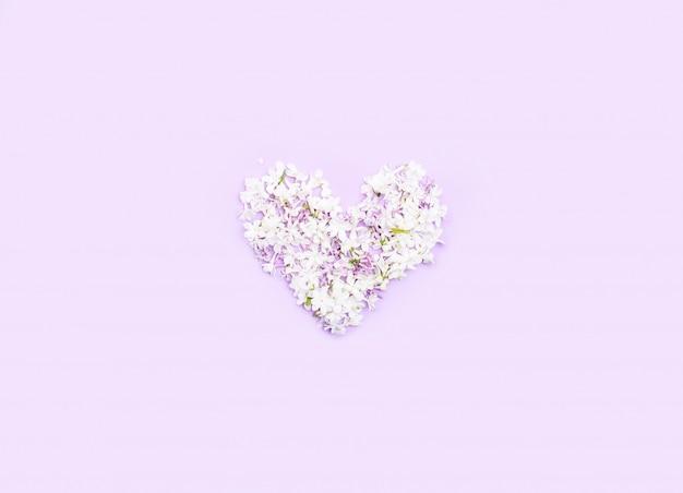 Il cuore è foderato con fiori lilla su uno sfondo chiaro. contenuto festivo.