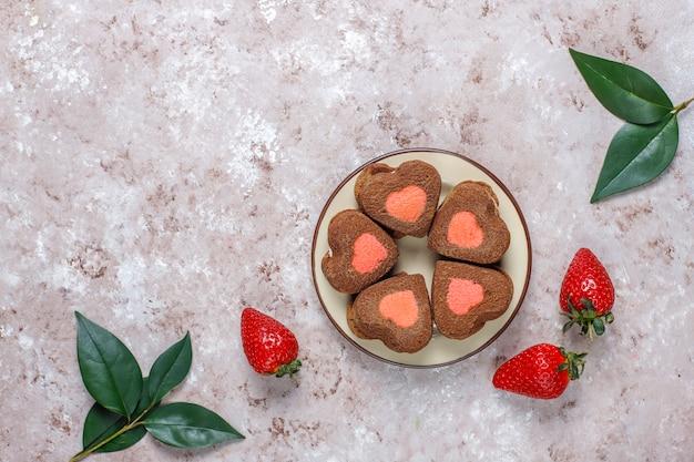 Il cuore ha modellato i biscotti con le fragole fresche, vista superiore della fragola e del cioccolato