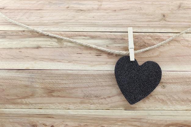 Il cuore nero ha appeso sulla corda della canapa isolata su fondo di legno.