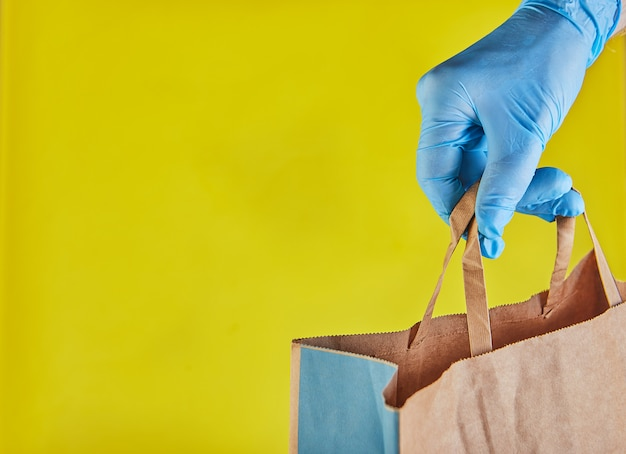 Il datore di lavoro del fattorino in guanti blu tiene il sacco di carta del mestiere con alimento, isolato. servizio quarantena pandemia coronavirus virus concept 2019-ncov. copia spazio. acquisti online