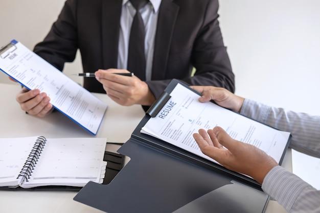 Il datore di lavoro o il reclutatore in possesso della lettura di un curriculum durante il colloquio sul suo profilo di candidato, il datore di lavoro in tuta sta conducendo un colloquio di lavoro, l'occupazione delle risorse del gestore e il concetto di assunzione