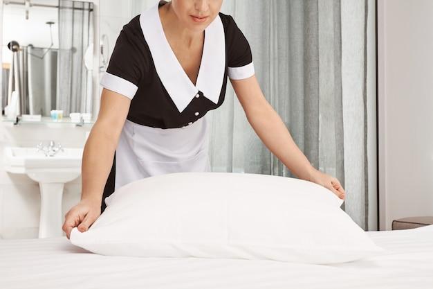 Il datore di lavoro sarà soddisfatto del risultato. ritagliata foto della cameriera che pulisce la camera da letto, rifà il letto e batte i cuscini per sembrare ordinata, riordinando la camera d'albergo prima che i nuovi visitatori si trasferiscano