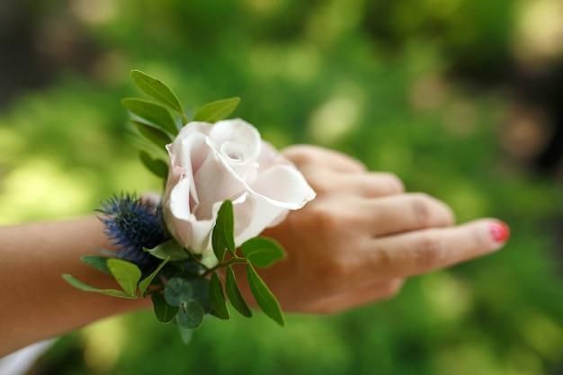 Il decoratore fiorista regge un braccialetto per damigella d'onore realizzato con rosa fresca