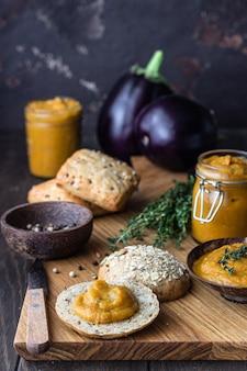 Il delizioso caviale di verdure in una ciotola e un barattolo di legno è servito con pane multicereali.