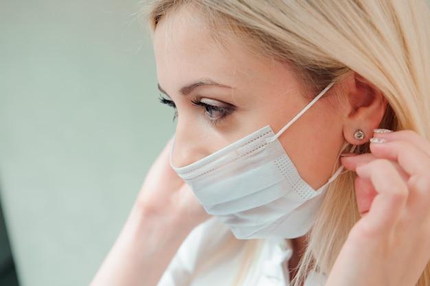 Il dentista adulto si mette una maschera protettiva sulla bocca.