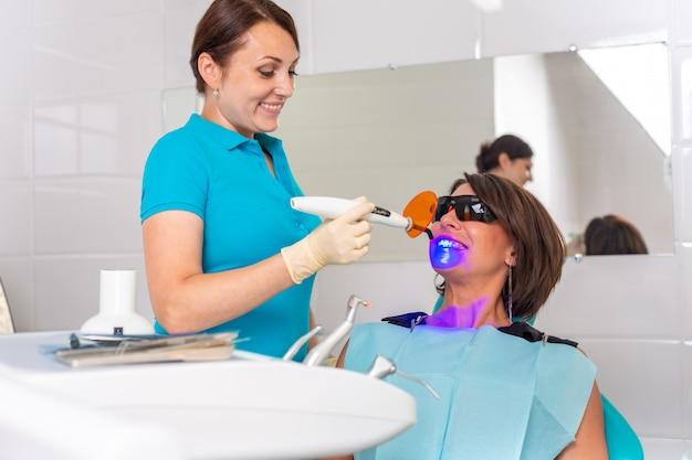 Il dentista brilla sui denti del paziente con una lampada a raggi ultravioletti per fissare il sigillo dentale.