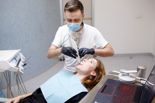 Il dentista esegue la scansione dei denti del paziente con uno scanner 3d.