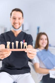 Il dentista maschio che mostra i denti modella la seduta davanti al paziente femminile