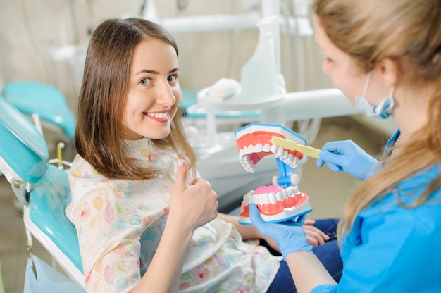 Il dentista mostra il modello della mascella dentale al paziente nella clinica del dentista