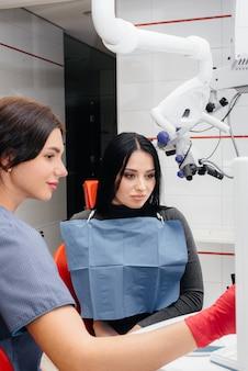 Il dentista mostra un'immagine dei denti del paziente e racconta il trattamento necessario. odontoiatria, salute.