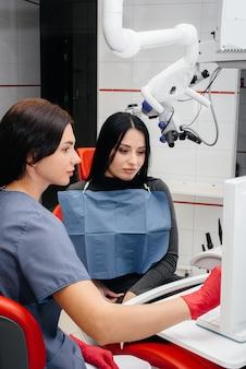 Il dentista mostra un'immagine dei denti del paziente e racconta il trattamento necessario
