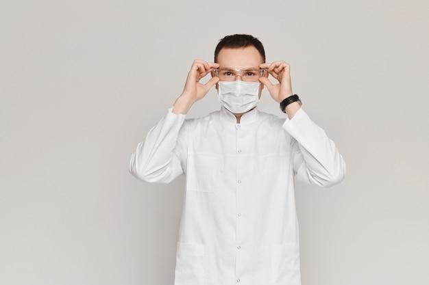 Il dentista o il medico bello indossa un abito medico bianco, una maschera e occhiali protettivi su grigio