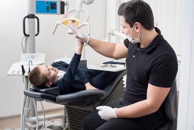 Il dentista pediatrico dà a cinque giovani ragazzi in studio dentistico