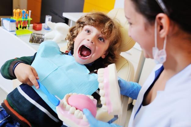 Il dentista racconta al bambino l'igiene orale e mostra una mascella e uno spazzolino artificiali