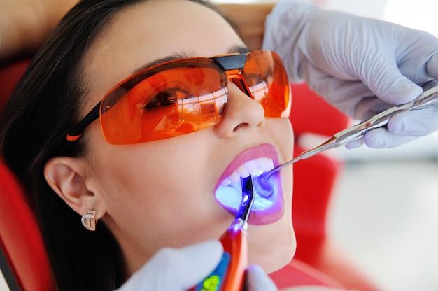 Il dentista sigilla il dente al paziente - una ragazza carina