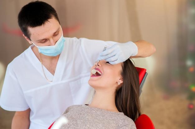 Il dentista sta trattando i denti con una bella ragazza.