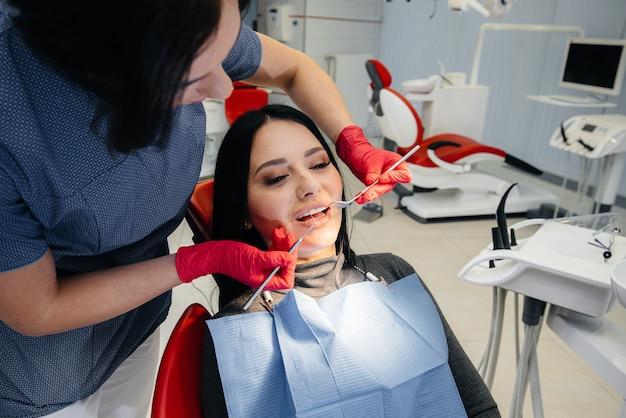 Il dentista tratta i denti della ragazza al paziente. odontoiatria