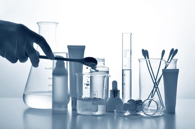 Il dermatologo formula e mescola la cura della pelle farmaceutica, i contenitori per flaconi per la cosmetica e la vetreria scientifica, ricerca e sviluppo del concetto di prodotto di bellezza.
