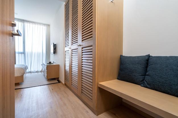 Il design degli interni di villa, casa, casa, condominio e appartamento dispone di armadio in legno, area salotto e cuscino blu nella camera da letto