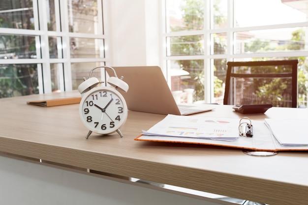 Il design del posto di lavoro nella stanza degli ufficiali ha un tavolo, un orologio, un computer portatile vicino alla finestra.