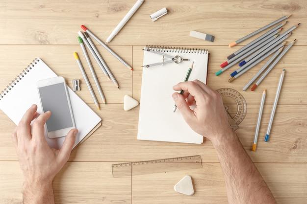 Il designer disegna uno schizzo su un quaderno su un tavolo di legno. stazionario. vista dall'alto