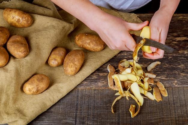 Il dettaglio della donna passa la sbucciatura della patata gialla fresca con lo sbucciatore della cucina