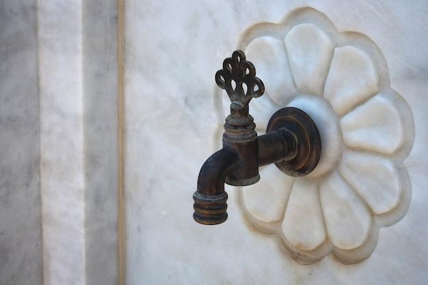 Il dettaglio di una valvola del rubinetto dell'acqua attorciglia le pareti di marmo.
