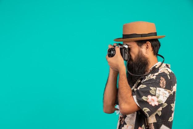 Il di un turista maschio con una lunga barba che indossa un cappello e in possesso di una macchina fotografica su un blu.