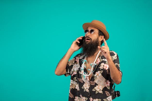 Il di un uomo con la barba lunga felice che indossa un cappello, indossa una camicia a righe, in possesso di un telefono su un blu.