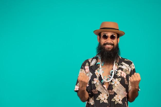 Il di un uomo felice con una lunga barba che indossa un cappello, indossa una camicia a righe che mostra un gesto su un blu.