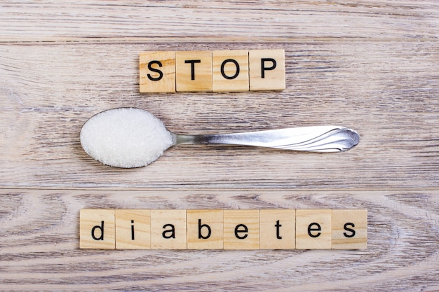 Il diabete stop blocca le lettere di legno e il mucchio di zucchero su un cucchiaio. concetto prevenzione del diabete
