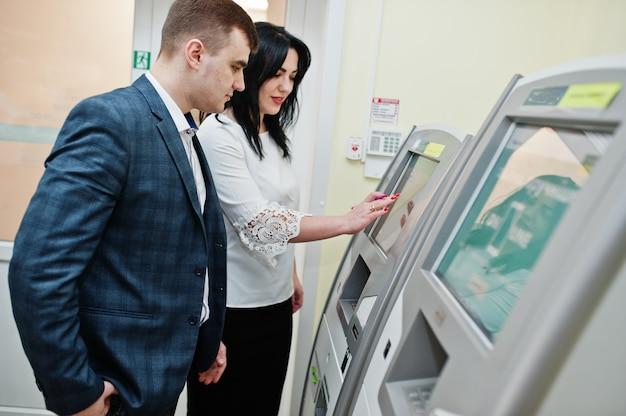 Il dipendente della banca spiega al cliente come lavorare con la macchina bancomat.