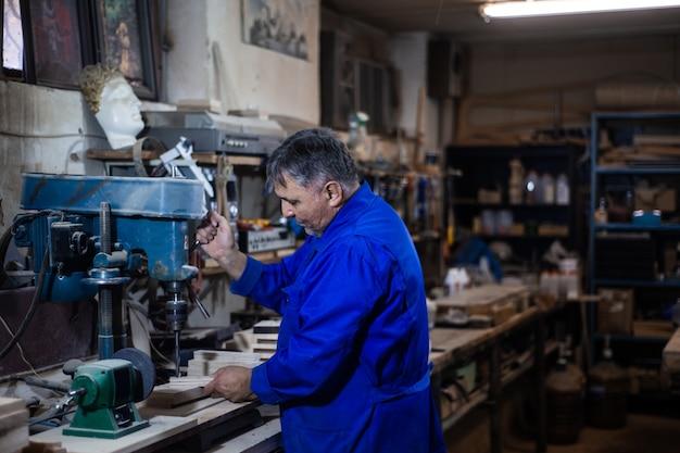 Il dipendente perfora l'oggetto in officina con l'aiuto di una pressa per perforazione