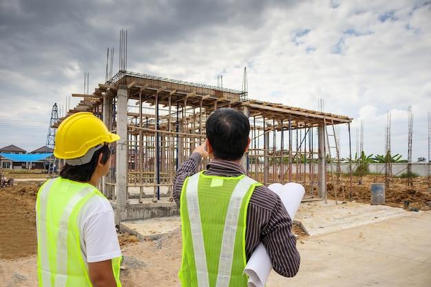 Il direttore di costruzione asiatico dell'uomo di affari e il lavoratore dell'ingegnere in casco protettivo tengono la carta delle cianografie a disposizione al cantiere della casa