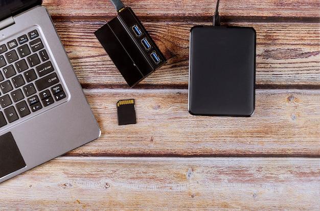Il disco rigido di backup esterno collegato al computer portatile trasferisce le foto nell'area di lavoro desktop del fotografo di schede sd