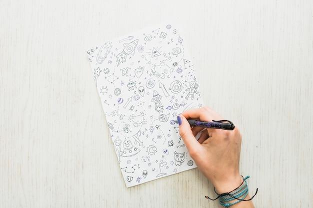 Il disegno della mano dell'artista femminile scarabocchia con la penna su carta sopra strutturato di legno